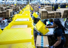 A woman works at a packing station at the 855,000-square-foot Amazon fulfillment center in Staten Island, one of the five boroughs of New York City, on February 5, 2019. - Inside a huge warehouse on Staten Island thousands of robots are busy distributing thousands of items sold by the giant of online sales, Amazon. (Photo by Johannes EISELE / AFP)        (Photo credit should read JOHANNES EISELE/AFP via Getty Images)
